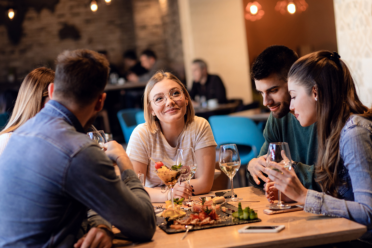 A young woman shares a restaurant table with friends.