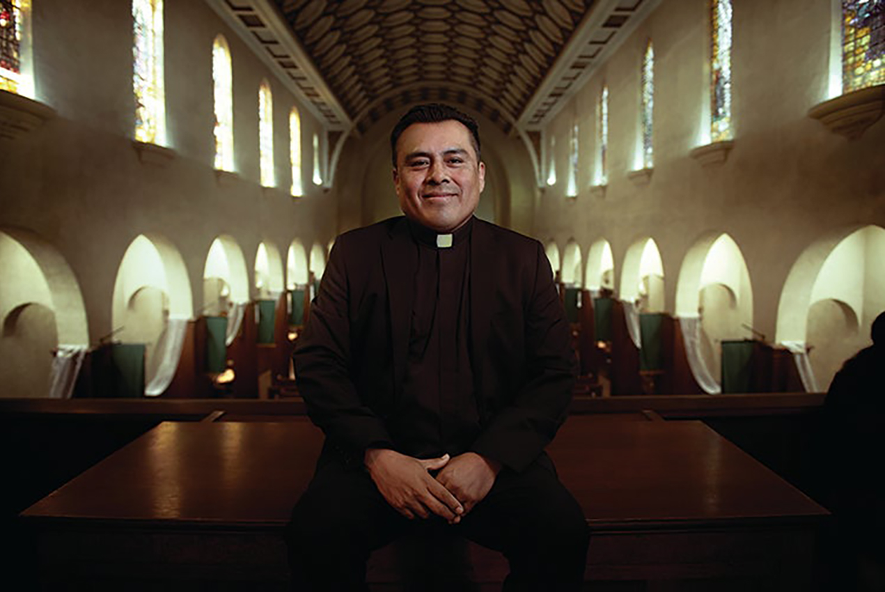 A young priest smiles in a cathedral.