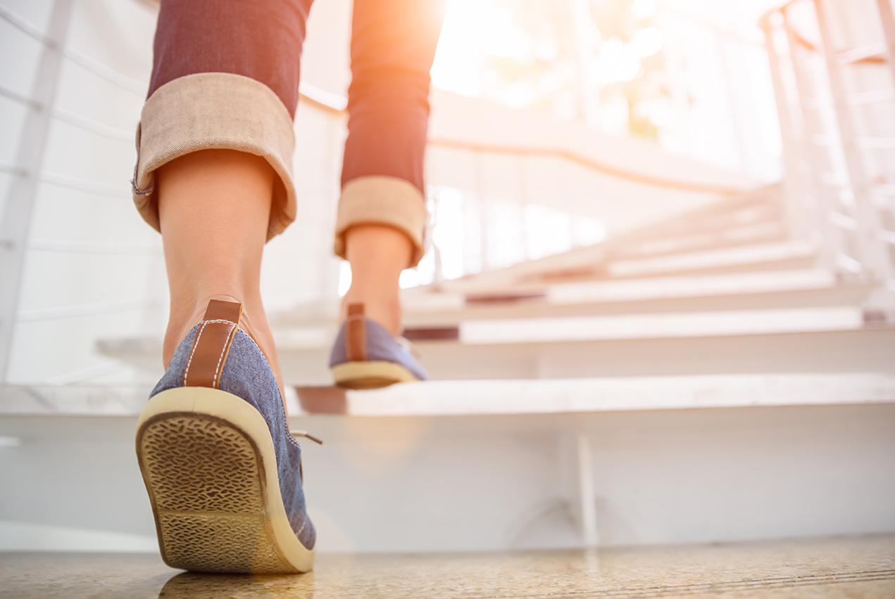Feet in sneakers walk up a sunlit stairway.